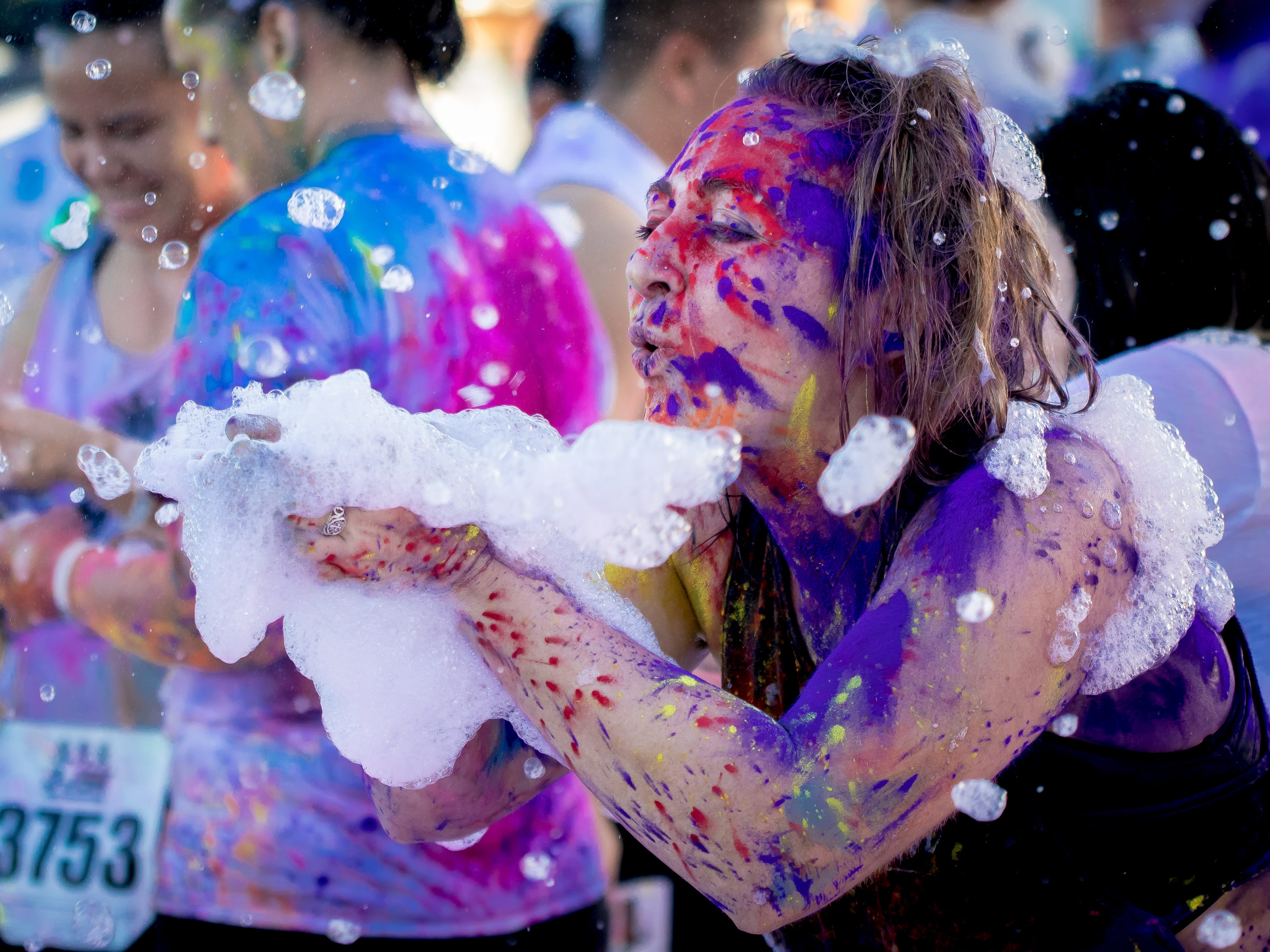 """Katherine Manyai blows bubbles away during the 13th Annual Triple J Family 10K/5K Run themed the """"Bubble Color Run"""" held  at Tripple J Complex in Tamuning on Nov.17.Virgilio Valencia /For Pacific Daily News"""