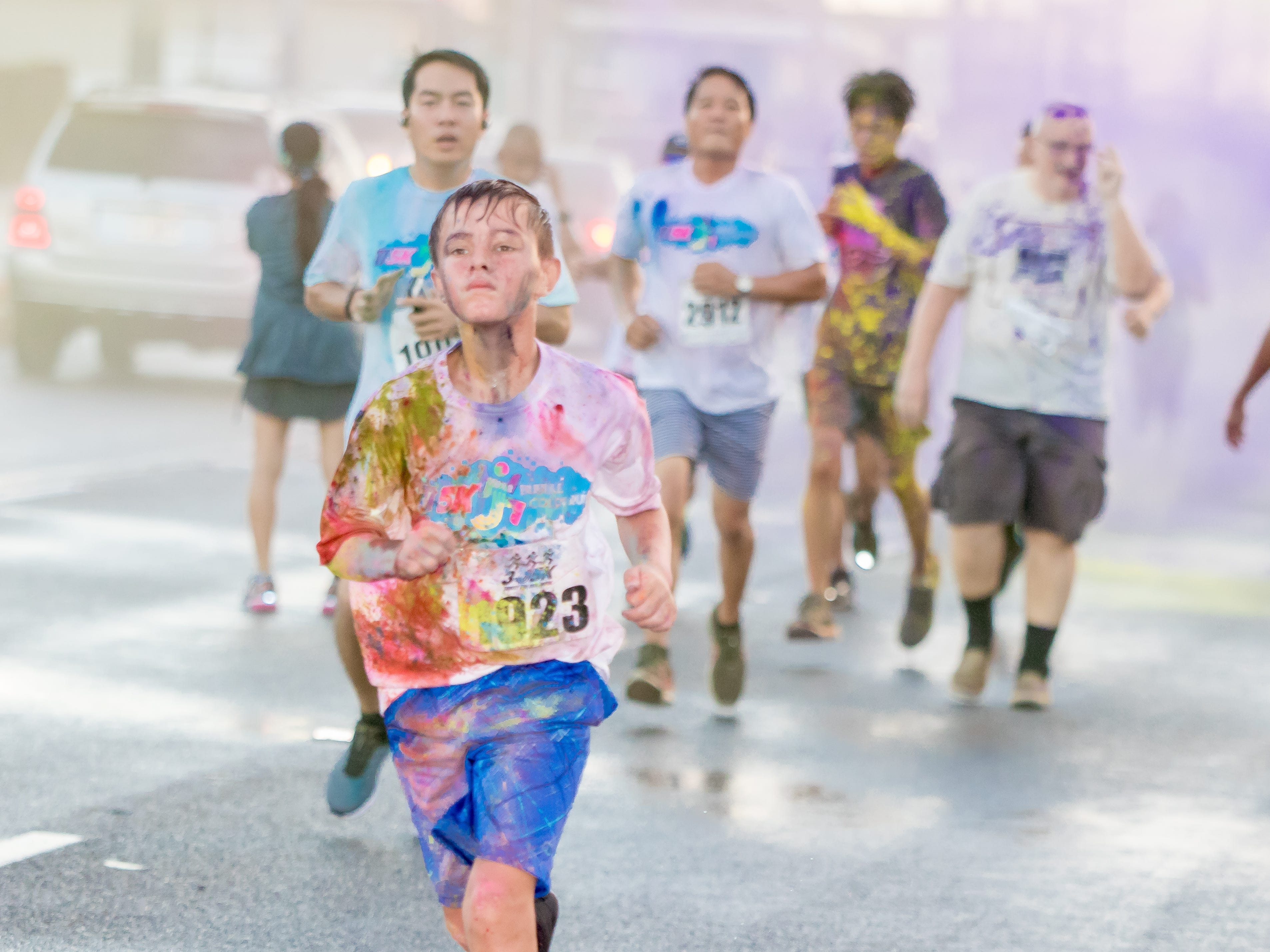 """A participants gets colorful as colored power is splashed on as they proceed the finish line during the 13th Annual Triple J Family 10K/5K Run themed the """"Bubble Color Run.""""Virgilio Valencia /For Pacific Daily News"""