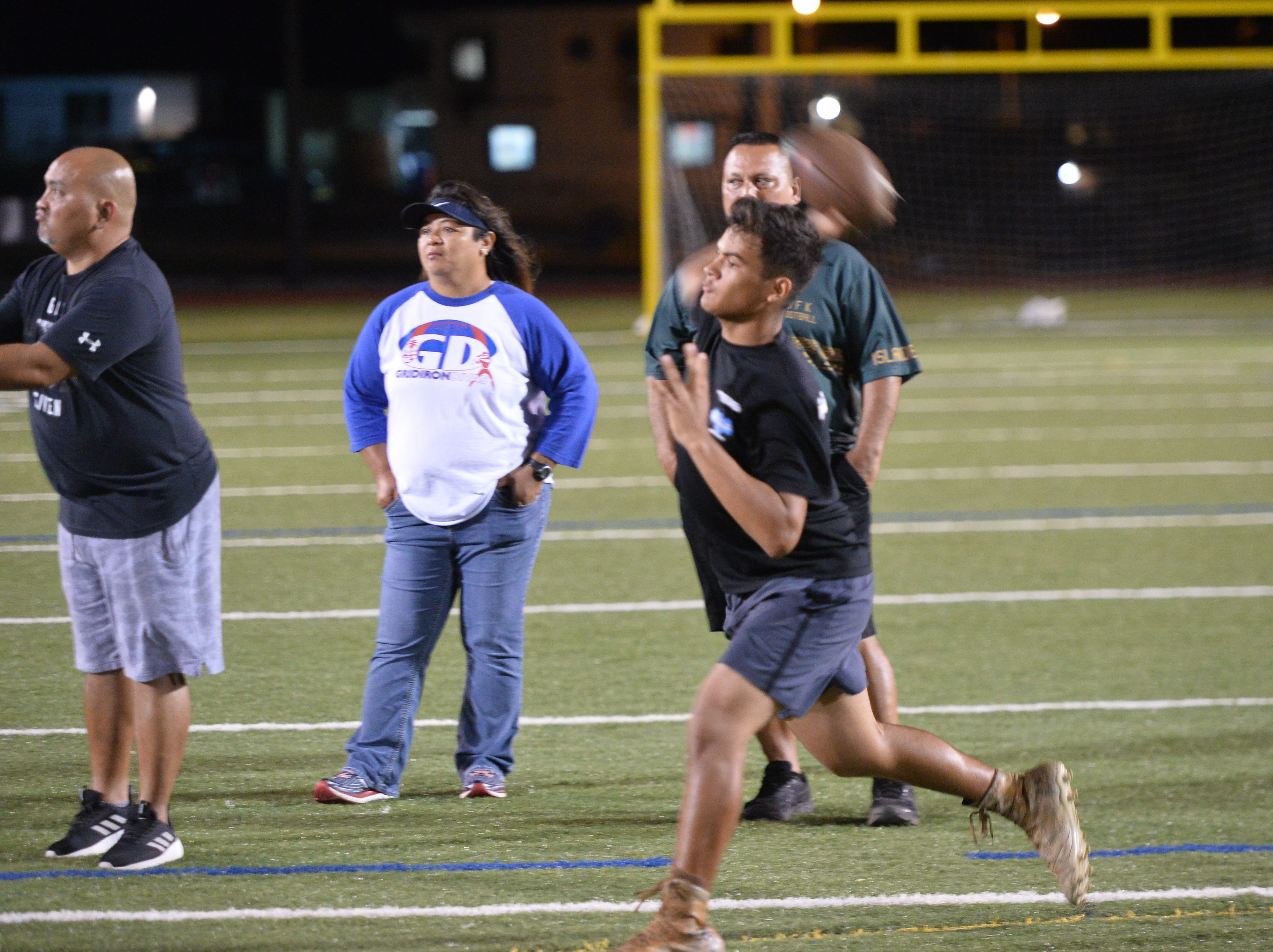 Andrew Perez zips a ball to a receiver under the watchful eye of his football coach Allen Blend, at rear.