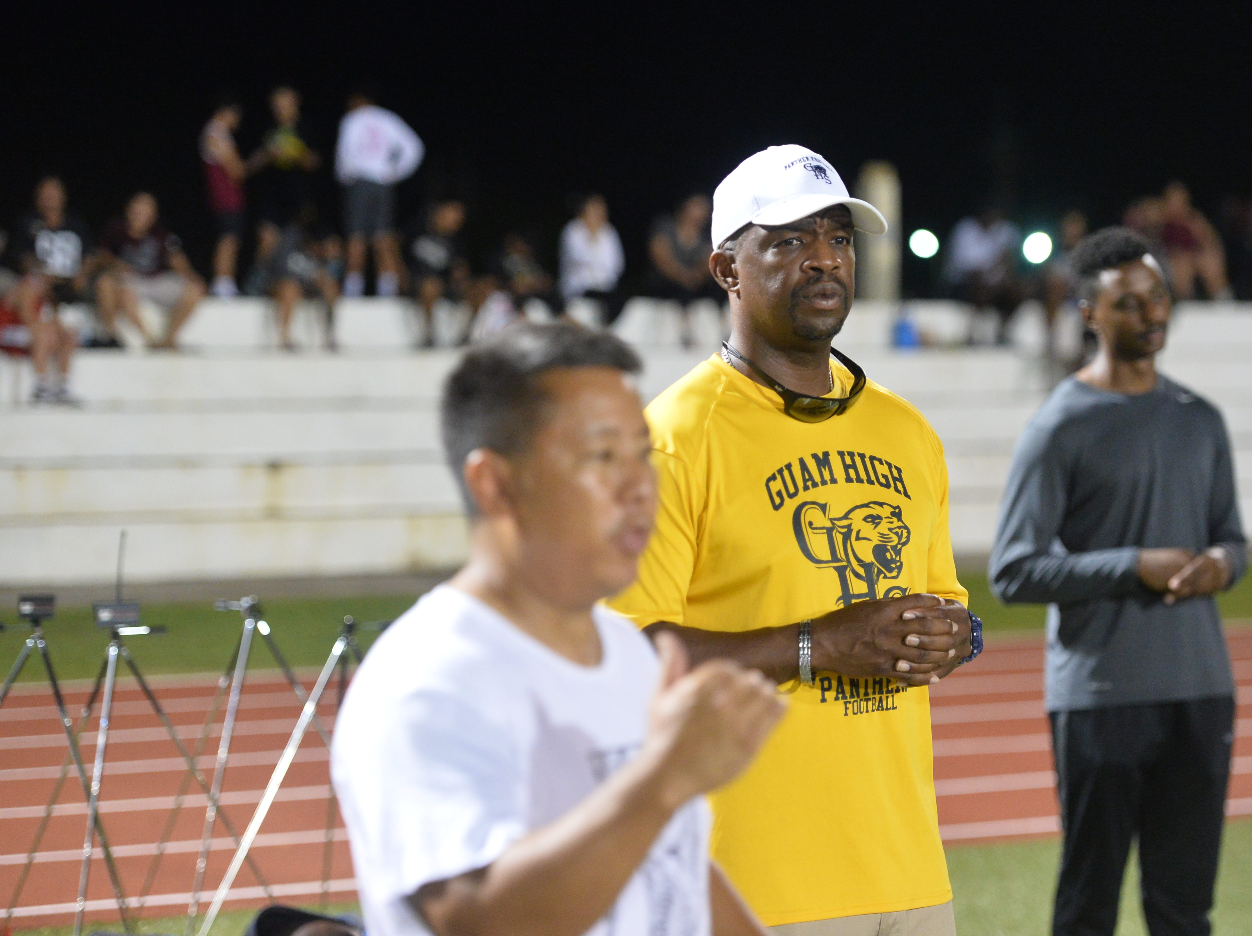 Guam High coach Jacob Dowdell, in yellow, watches the group gathered in front of coach Chad Ikei, at left.