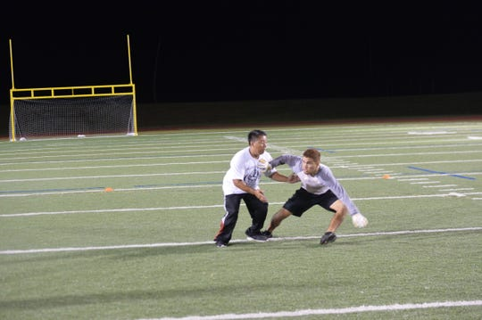 Chase Spotanski, right, works on receiving routes with Chad Ikei, one of several volunteers who worked with football players during the College Football Showcase and Combine Nov. 14 at Guam High.