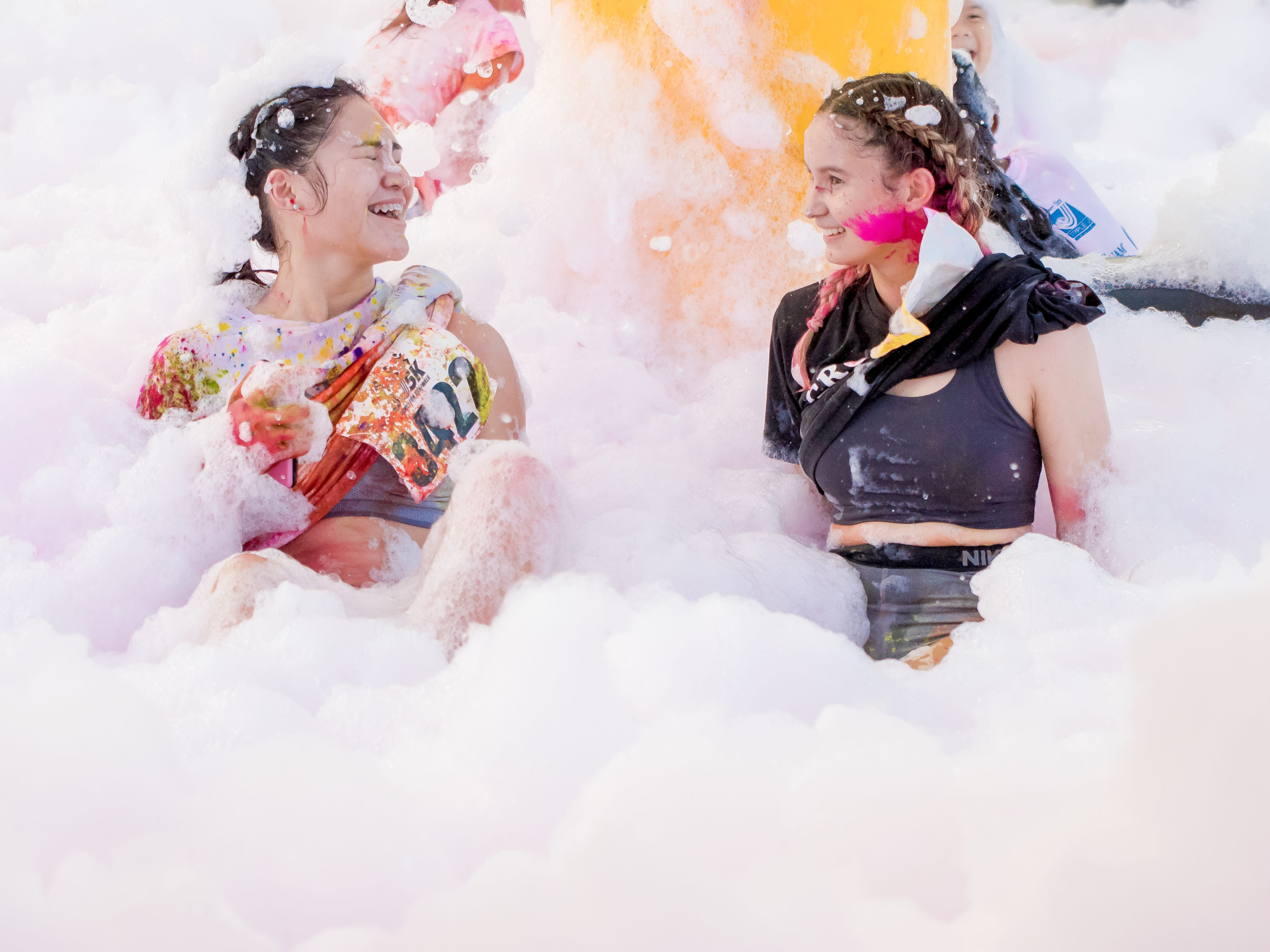 """Angeline del Carmen and Marina Flores soak in bubble foam during the 13th Annual Triple J Family 10K/5K Run themed the """"Bubble Color Run"""" held  at Tripple J Complex in Tamuning on Nov.17.Virgilio Valencia /For Pacific Daily News"""