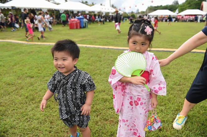 Aiko Inagaki, 3, and her brother Kiichi Inagaki, 1, are forced into posing for a picture during the 39th Japan Autumn Festival at the Gov. Joseph A. Flores Memorial Park in Tumon, Nov. 17, 2018.