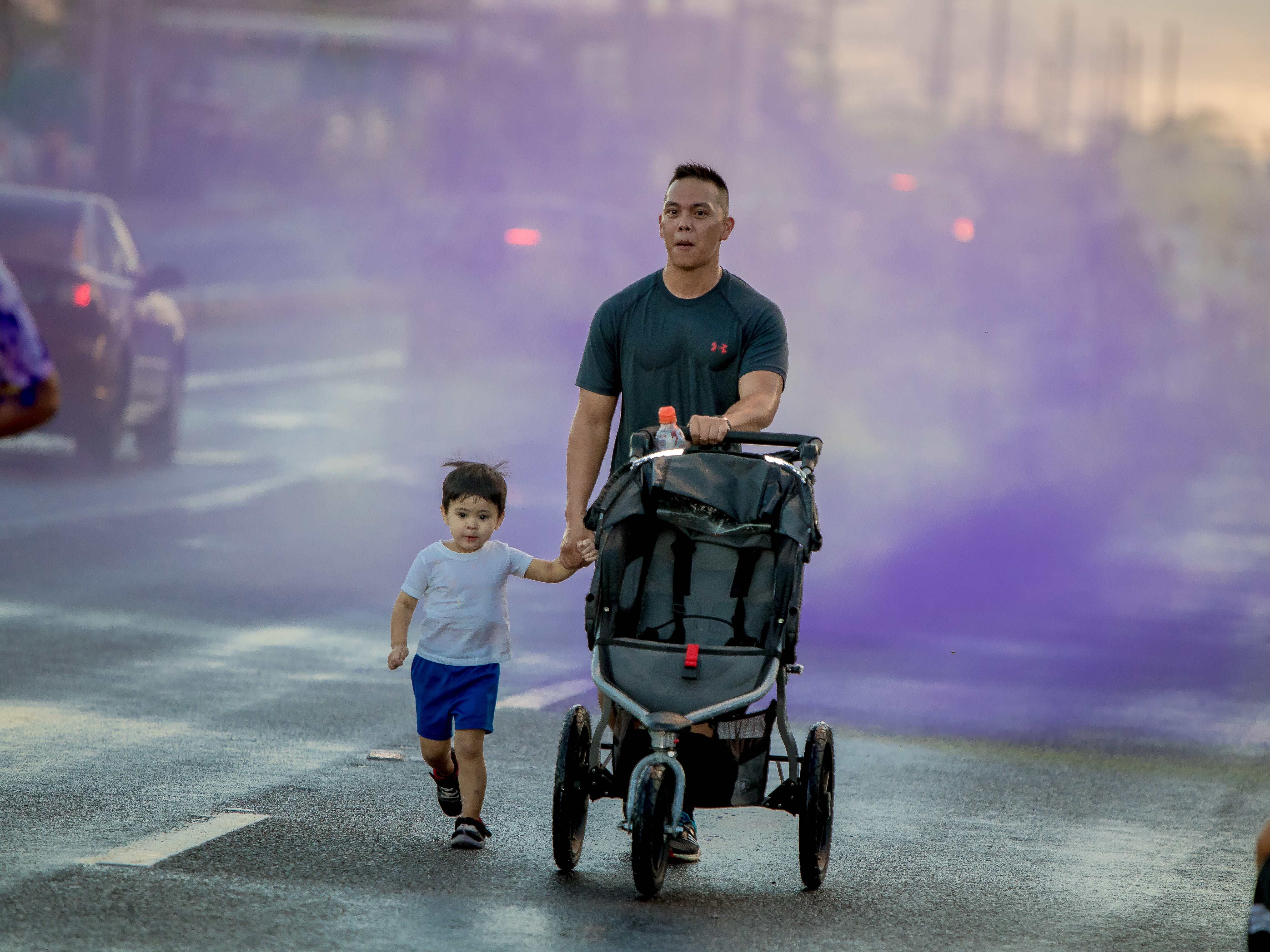 A kid gets off the stroller as they approach the finish line.Virgilio Valencia /For Pacific Daily News