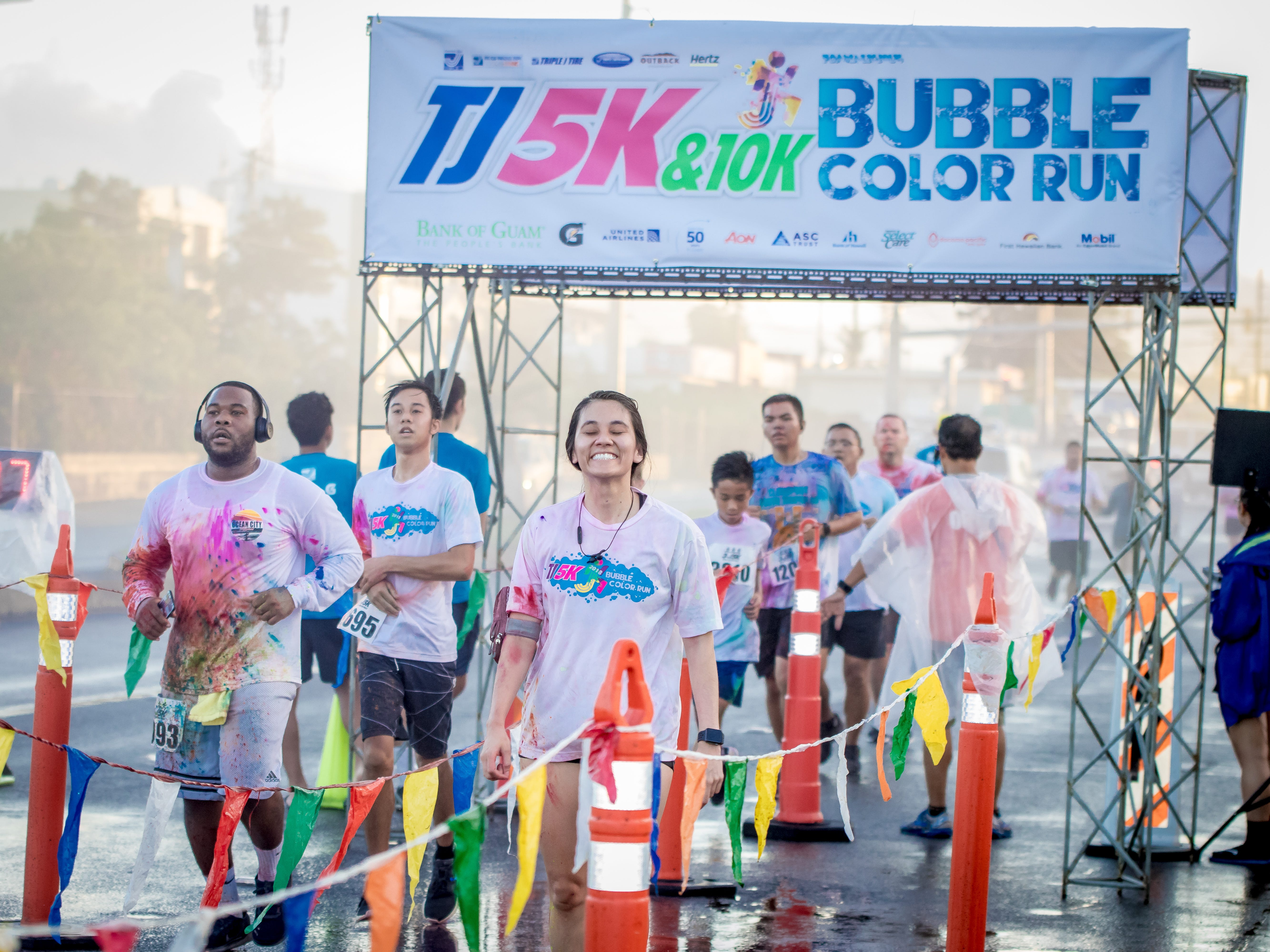 """Participants return to the finish line during the  13th Annual Triple J Family 10K/5K Run themed the """"Bubble Color Run""""Virgilio Valencia /For Pacific Daily News"""