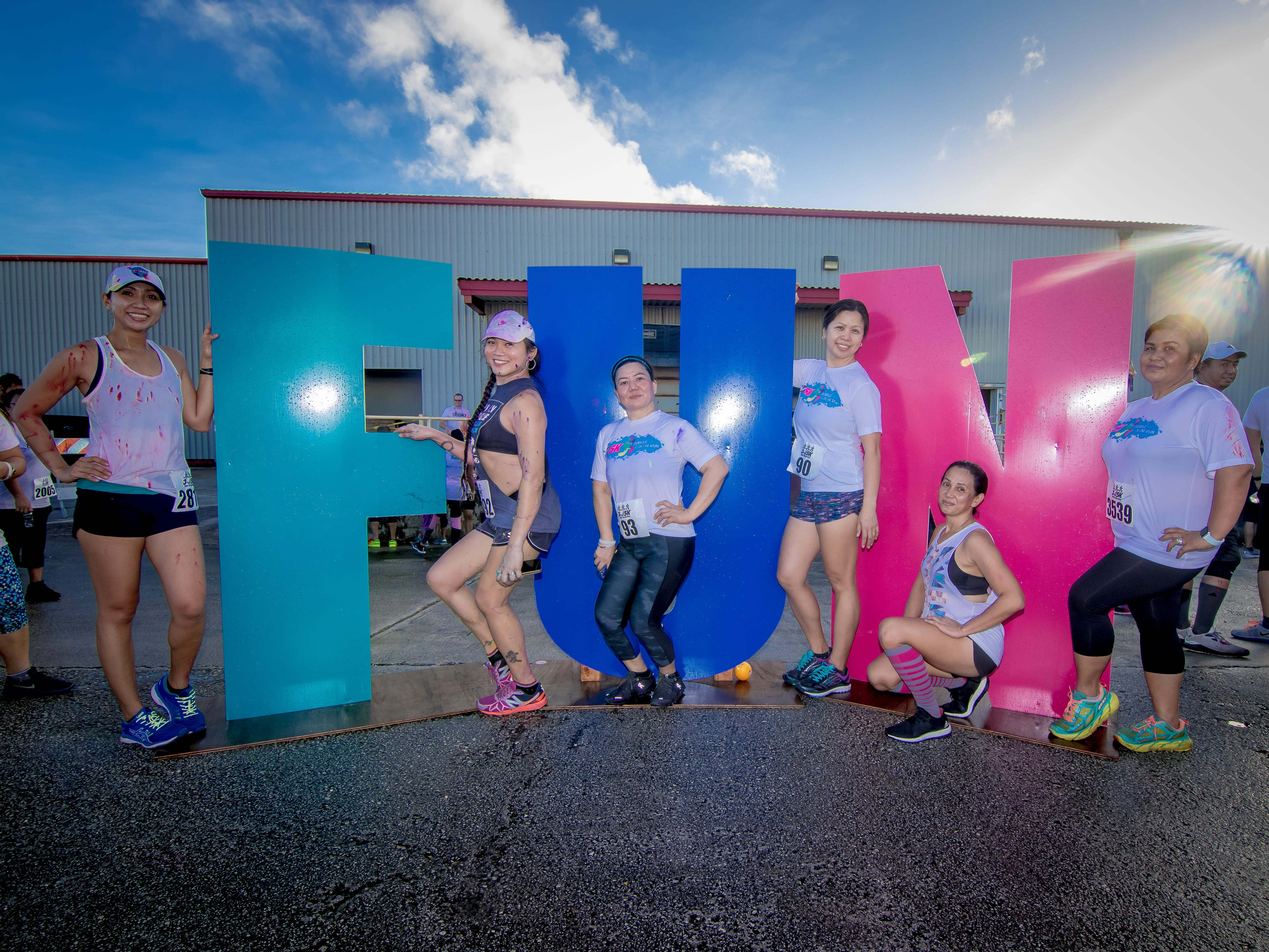 """Aileen Honrado, Kitkat Casin, Chit Cabanting, Tez Schmidt, Chato Camaganacan, and Jhoane Antonio pose at the display signs during the 13th Annual Triple J Family 10K/5K Run themed the """"Bubble Color Run"""" held  at Tripple J Complex in Tamuning on Nov.17."""