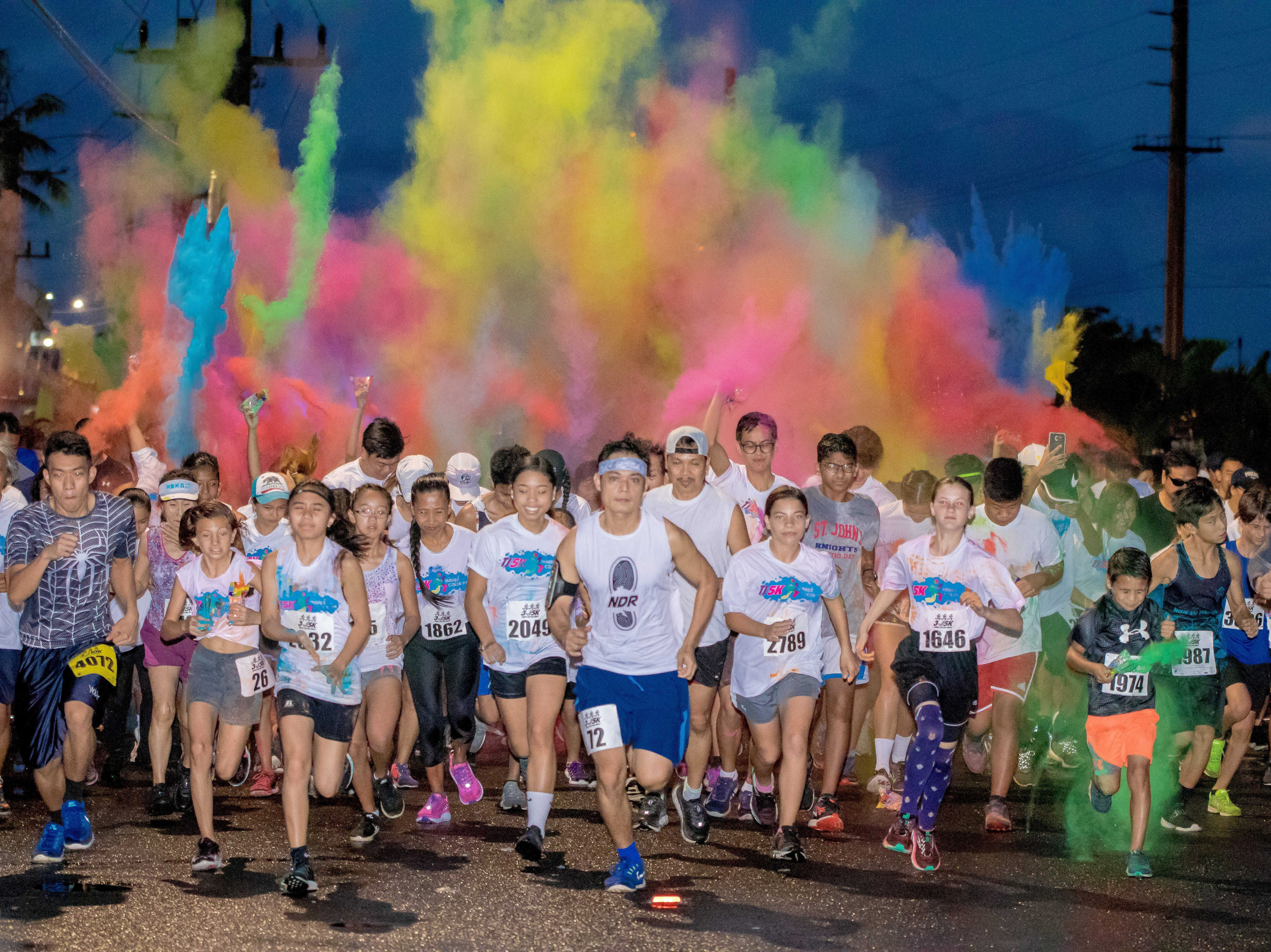 """Powdered colors brighten the dark skies as 5k participants take off during the start of the 13th Annual Triple J Family 10K/5K Run themed the """"Bubble Color Run"""" held at Tamuning on Nov. 17. Virgilio Valencia /For Pacific Daily News"""