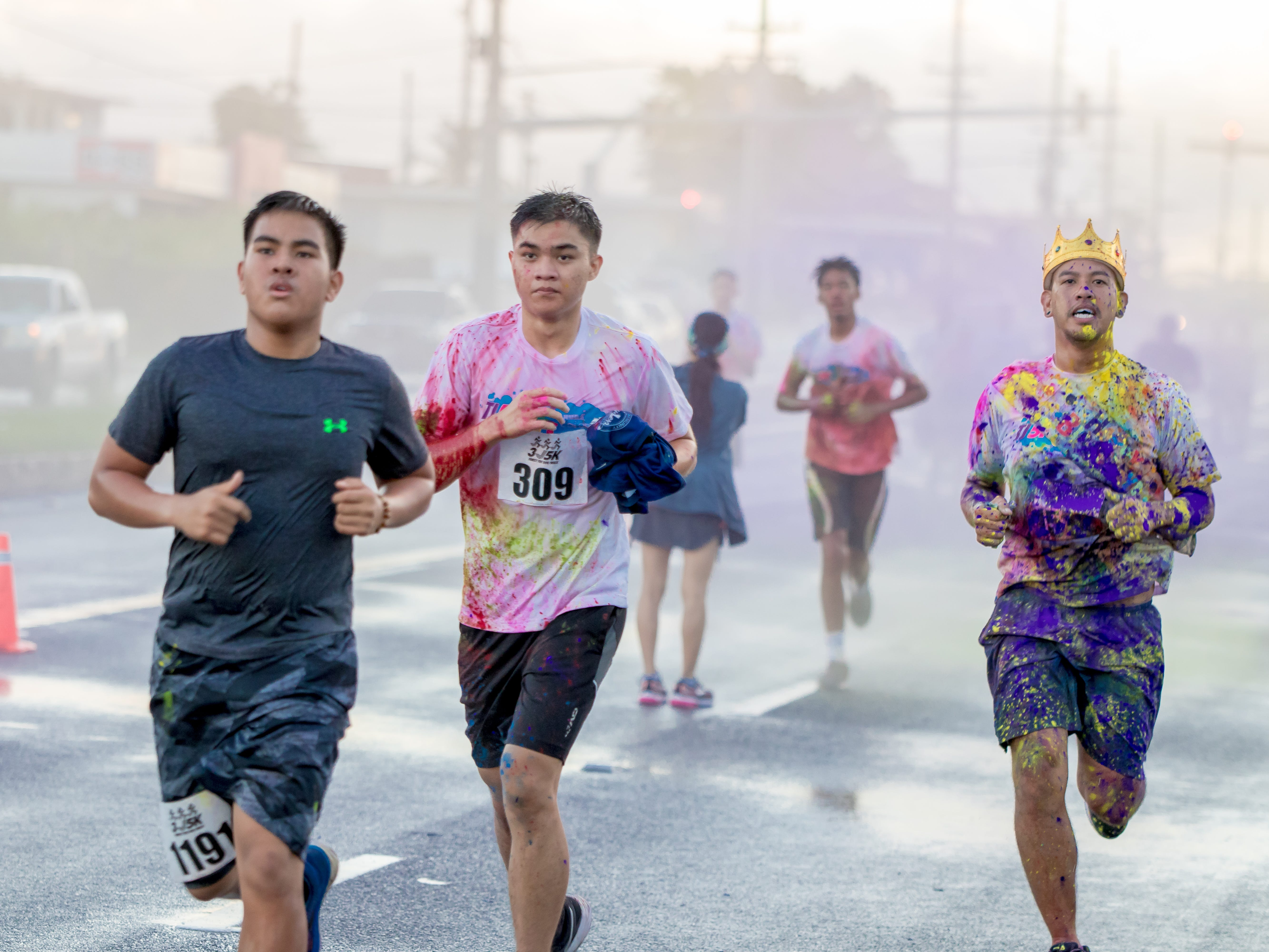 """Participants gets colorful as colored power is splashed as they proceed the finish line during the 13th Annual Triple J Family 10K/5K Run themed the """"Bubble Color Run.""""Virgilio Valencia /For Pacific Daily News"""