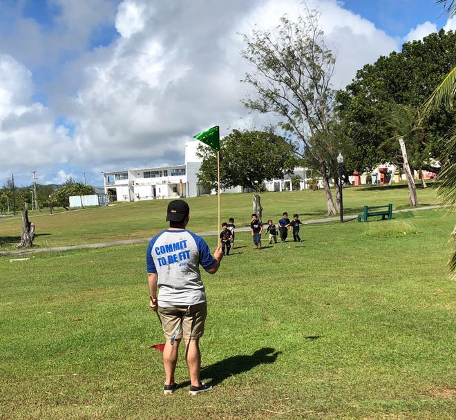 A University of Guam volunteer flags down children in a foot race at the 4th Annual Fun in the Sun event, which brings awareness to diabetes prevention.