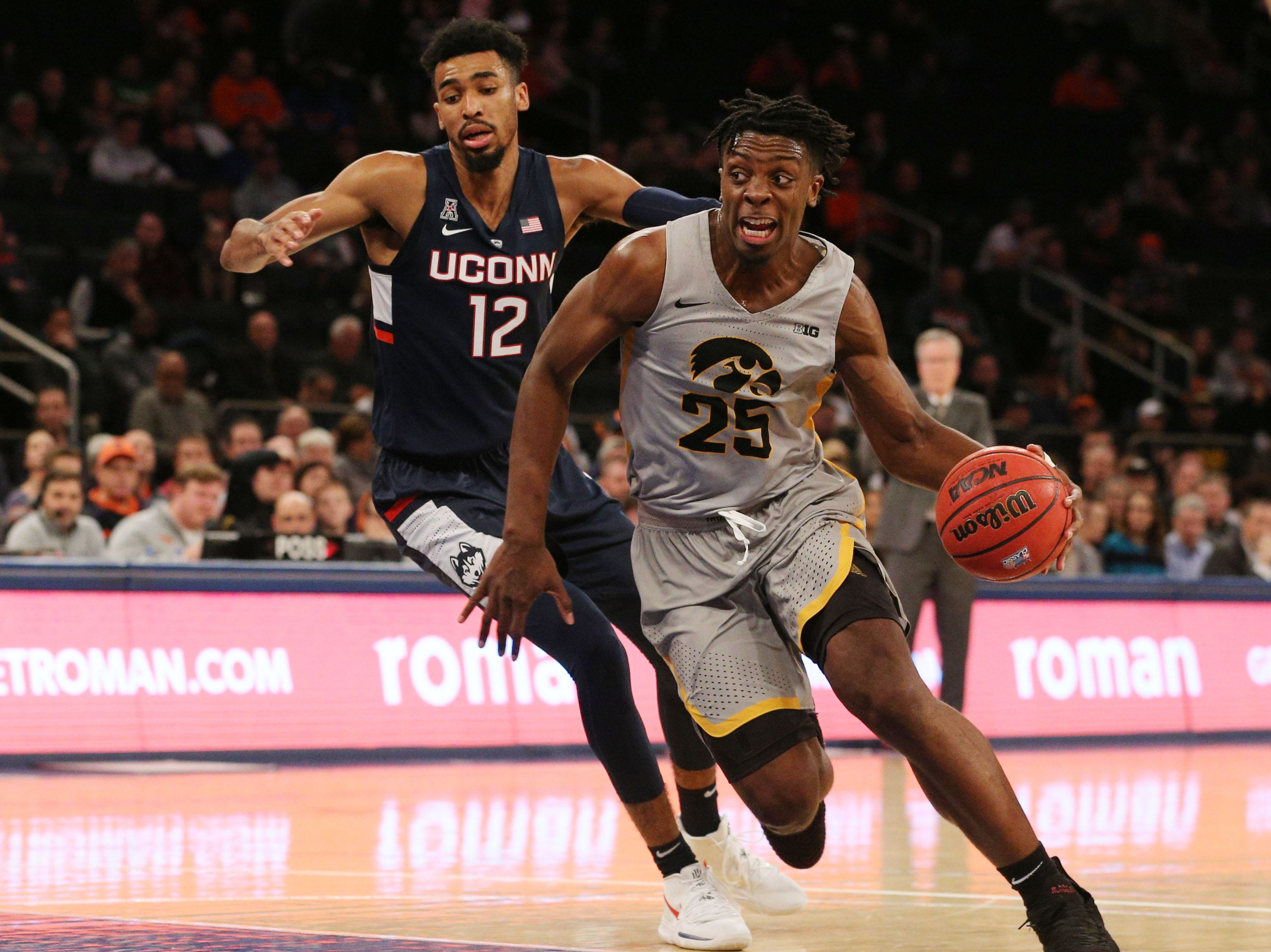 Nov 16, 2018; New York, NY, USA; Iowa Hawkeyes forward Tyler Cook (25) drives around Connecticut Huskies forward Tyler Polley (12) during the first half at Madison Square Garden. Mandatory Credit: Brad Penner-USA TODAY Sports