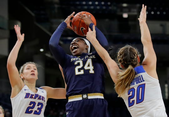 Notre Dame's Arike Ogunbowale, center, goes to the basket between DePaul's Dee Bekelja, left, and Kelly Campbell during the first half of an NCAA college basketball game, Saturday, Nov. 17, 2018, in Chicago.