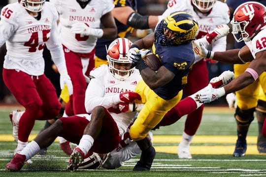 Michigan Wolverines running back Karan Higdon is tackled by Indiana Hoosiers defensive back Jonathan Crawford (9) in the first half at Michigan Stadium, Nov. 17, 2018.