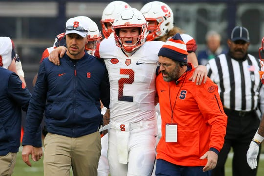 Syracuse Orange quarterback Eric Dungey (2) is helped off the field after being injured against the Notre Dame Fighting Irish during the first quarter at Yankee Stadium.