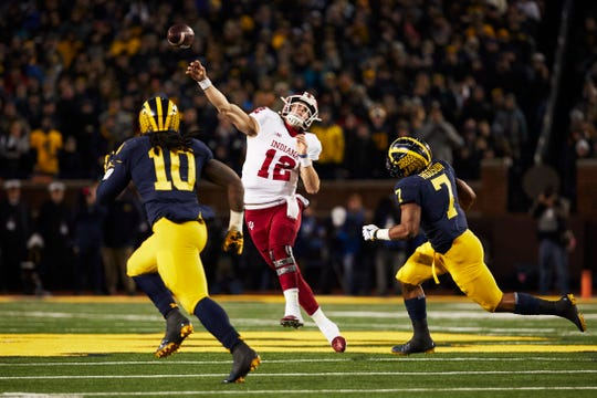 Indiana Hoosiers quarterback Peyton Ramsey (12) passes under pressure by Michigan Wolverines linebacker Khaleke Hudson (7) over linebacker Devin Bush (10) in the first half at Michigan Stadium.