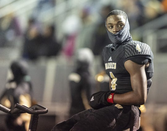 Warren Central senior David Bell (4) keeps his legs warm on the sideline by riding a stationary bike during the first half of action. He briefly returned to the game, but finished watching from the sidelines.