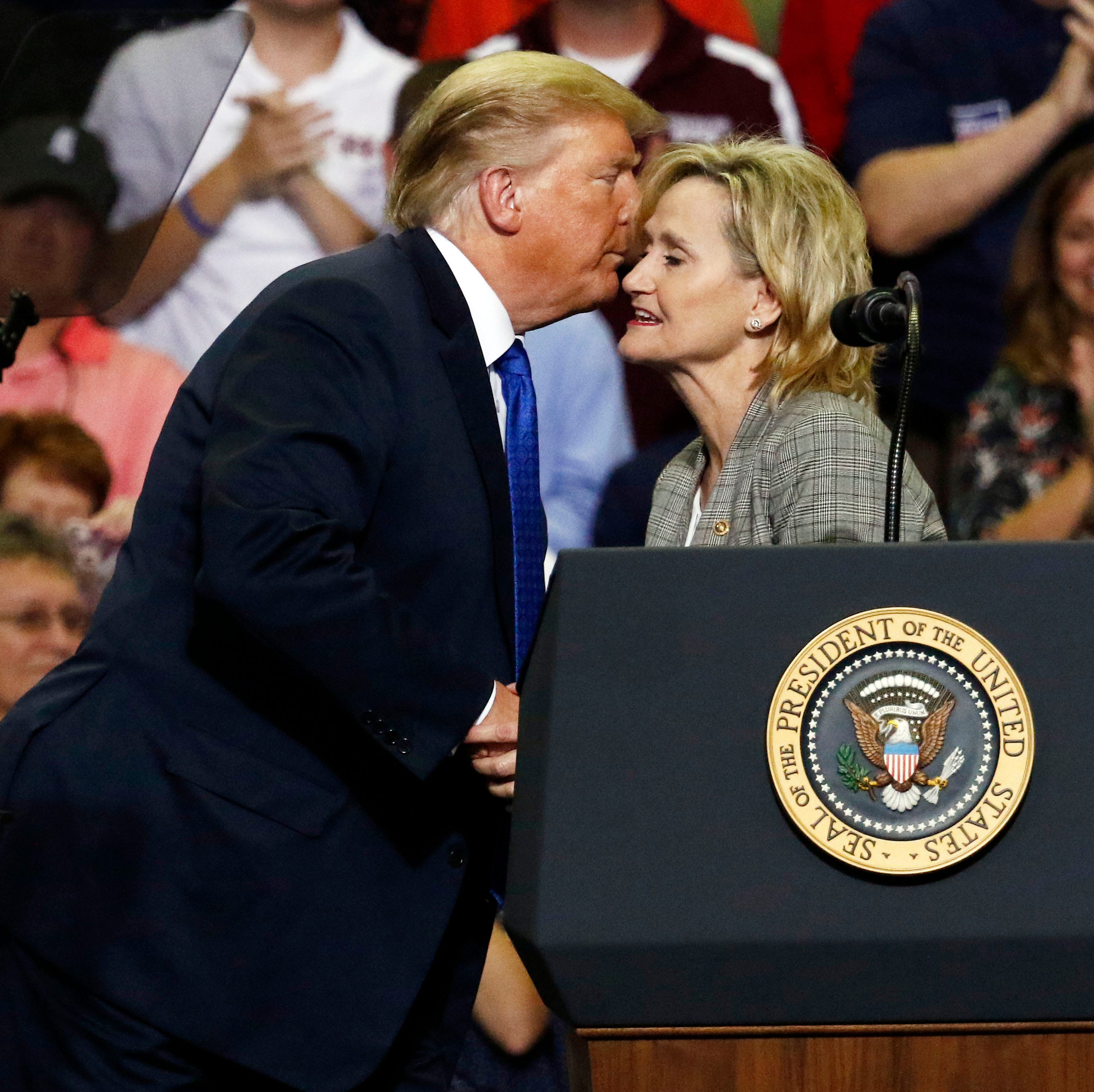 President Donald Trump kisses Sen. Cindy Hyde-Smith, R-Miss., after introducing her at a rally Tuesday, Oct. 2, 2018, in Southaven, Miss.  (AP Photo/Rogelio V. Solis)