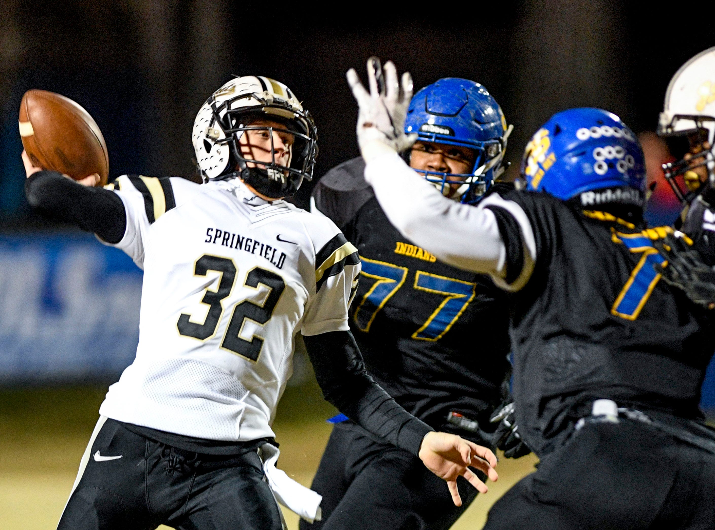 Springfield's Bryan Hayes (32) manages to let off a throw before being tackled by North Side's Steve Collins (7) and North Side's Jordan Williams (77) during a TSSAA playoff football game between Jackson North Side and Springfield High Schools at North Side High School in Jackson, Tenn., on Friday, Nov. 16, 2018.