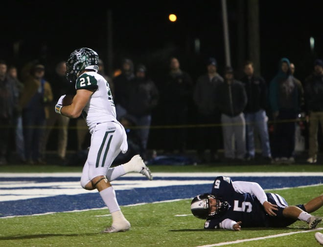 Greeneville's Cameron Hite (21) runs past Anderson County's Zach Wax (5) during the Anderson County versus Greeneville TSSAA play-off high school football game at Anderson County high school in Anderson County Friday Nov. 16 2018.