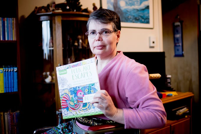 Jeanne Schubert holds her coloring books at her apartment in Broadway Towers in Maryville, Tennessee on Thursday, November 8, 2018.