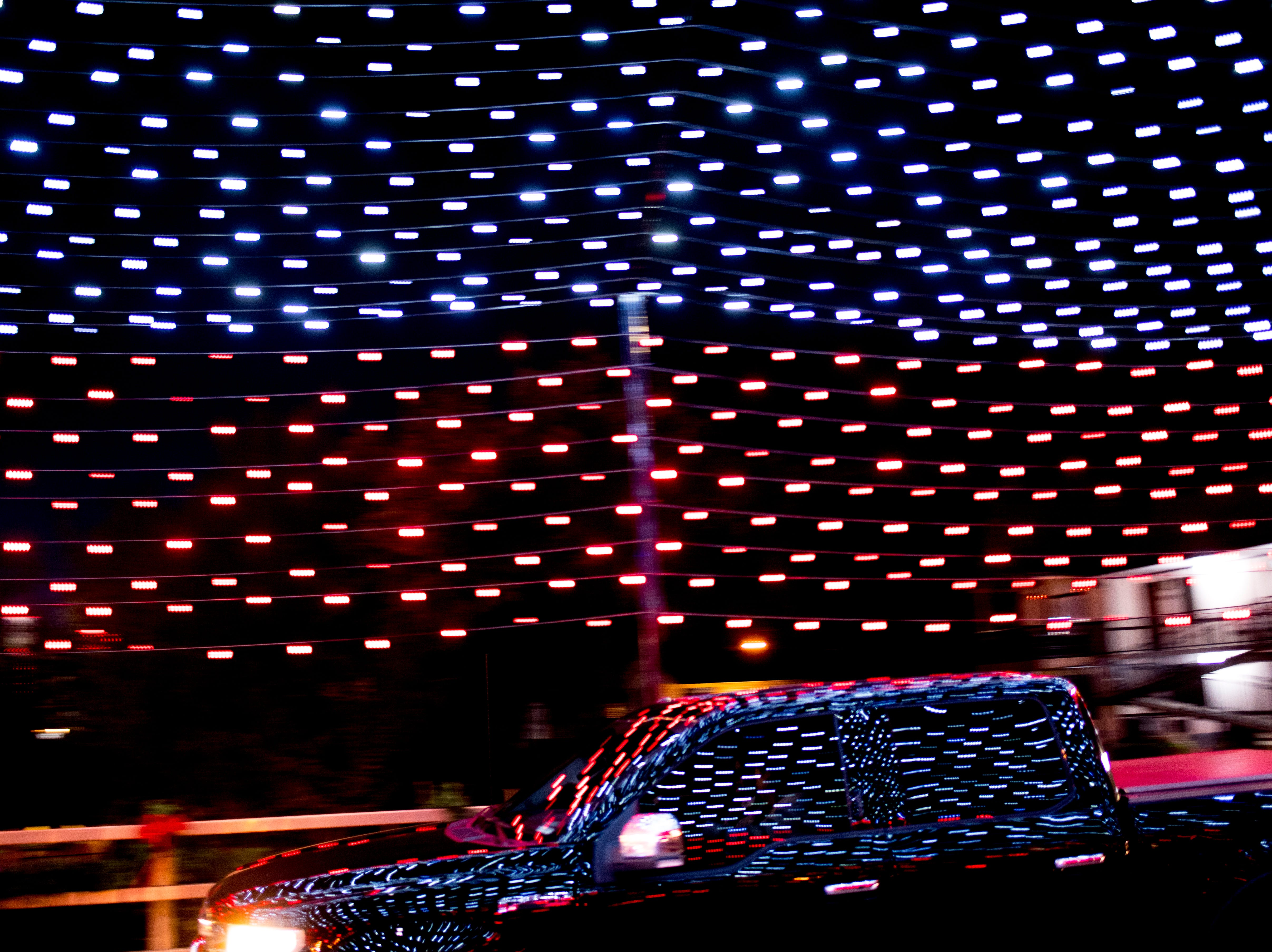 A car passes through the illuminated Old Mill Bridge during the annual Winterfest holiday lights display in Pigeon Forge, Tennessee on Friday, November 16, 2018.