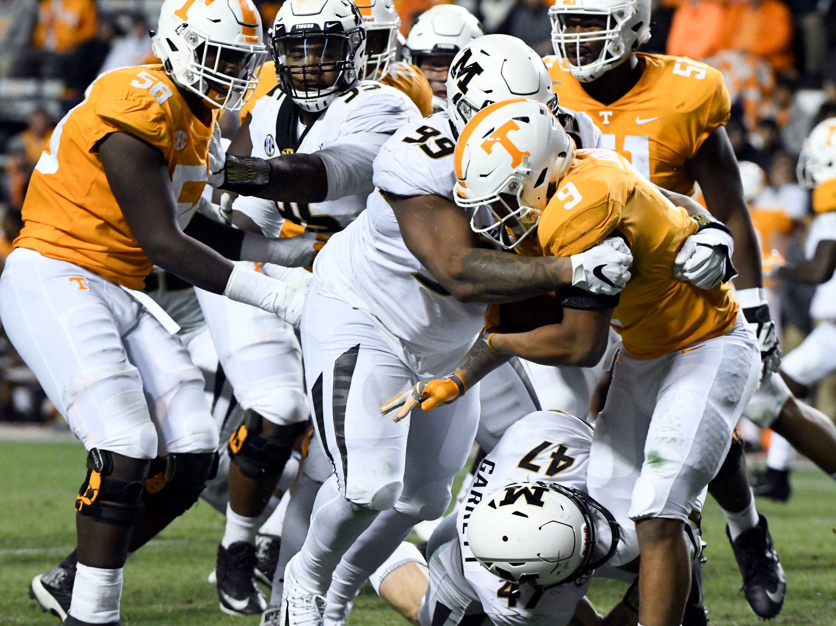 Tennessee running back Tim Jordan (9) is wrapped up by Missouri defensive lineman Walter Palmore (99) during the Tennessee and Missouri football game on Saturday, November 17, 2018.