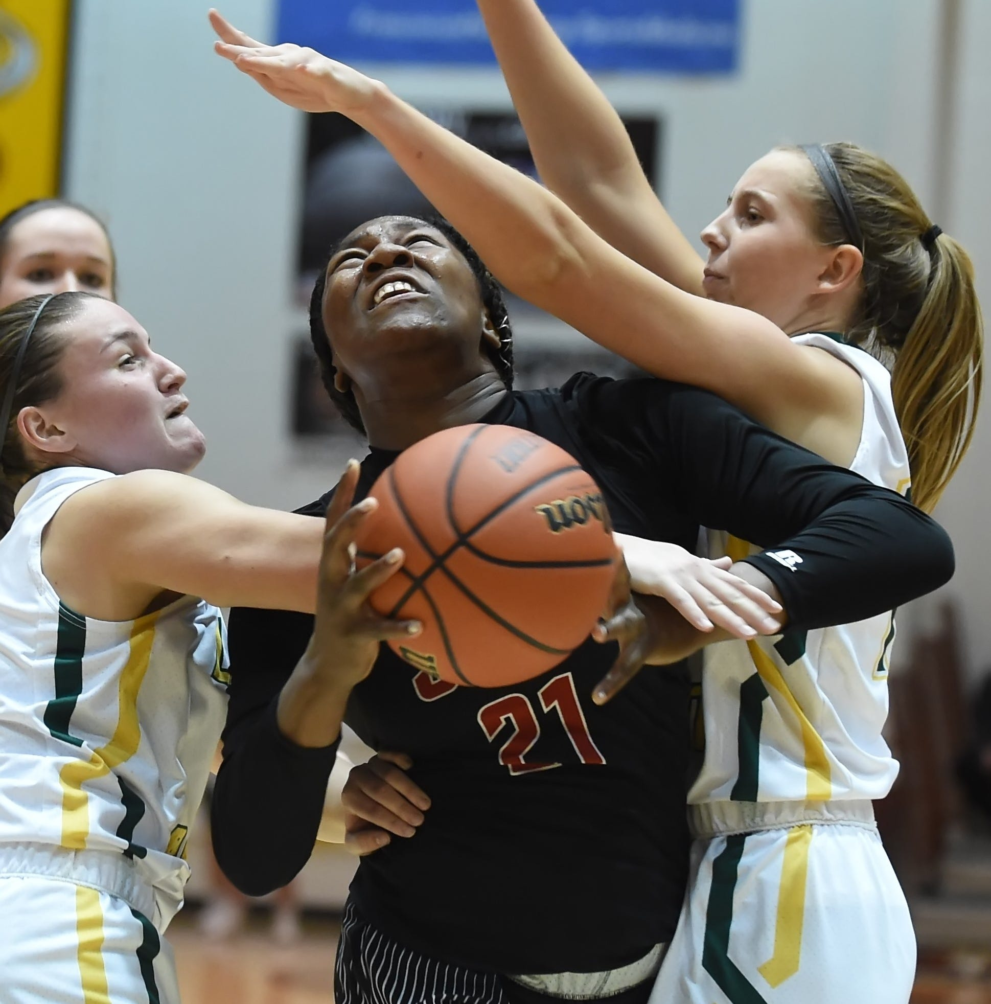 Lafayette Jeff junior forward Kiara Lewis drives through a pair of Benton Central defenders Friday night at the Franciscan Health Hoops Classic.