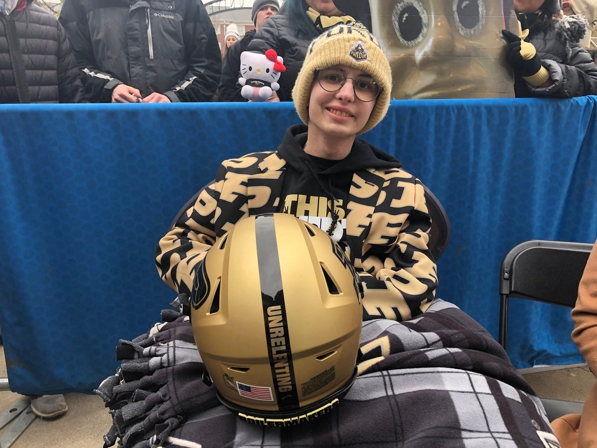 Purdue student Tyler Trent sits with a Purdue football helmet that shows one of the words he said describes what it means to be a Boilermaker.
