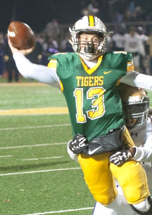 """St. Xavier quarterback Edgar """"Jack"""" Sivori tries to throw while wrapped up by a Male defender during the Class 6a Regional final between St. Xavier and Male at St. X's Br. Thomas More Stadium."""