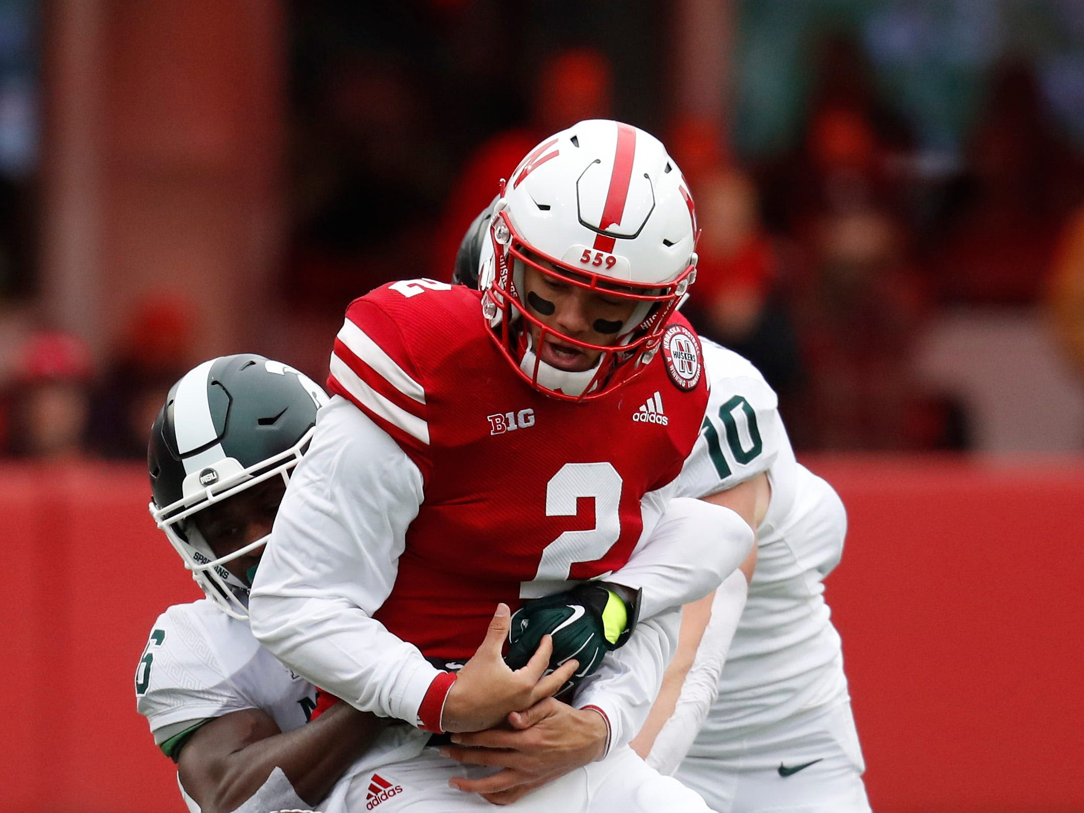 Nov 17, 2018; Lincoln, NE, USA; Nebraska Cornhuskers quarterback Adrian Martinez (2) fumbles the ball against Michigan State Spartans safety David Dowell (6) in the first half at Memorial Stadium. Mandatory Credit: Bruce Thorson-USA TODAY Sports