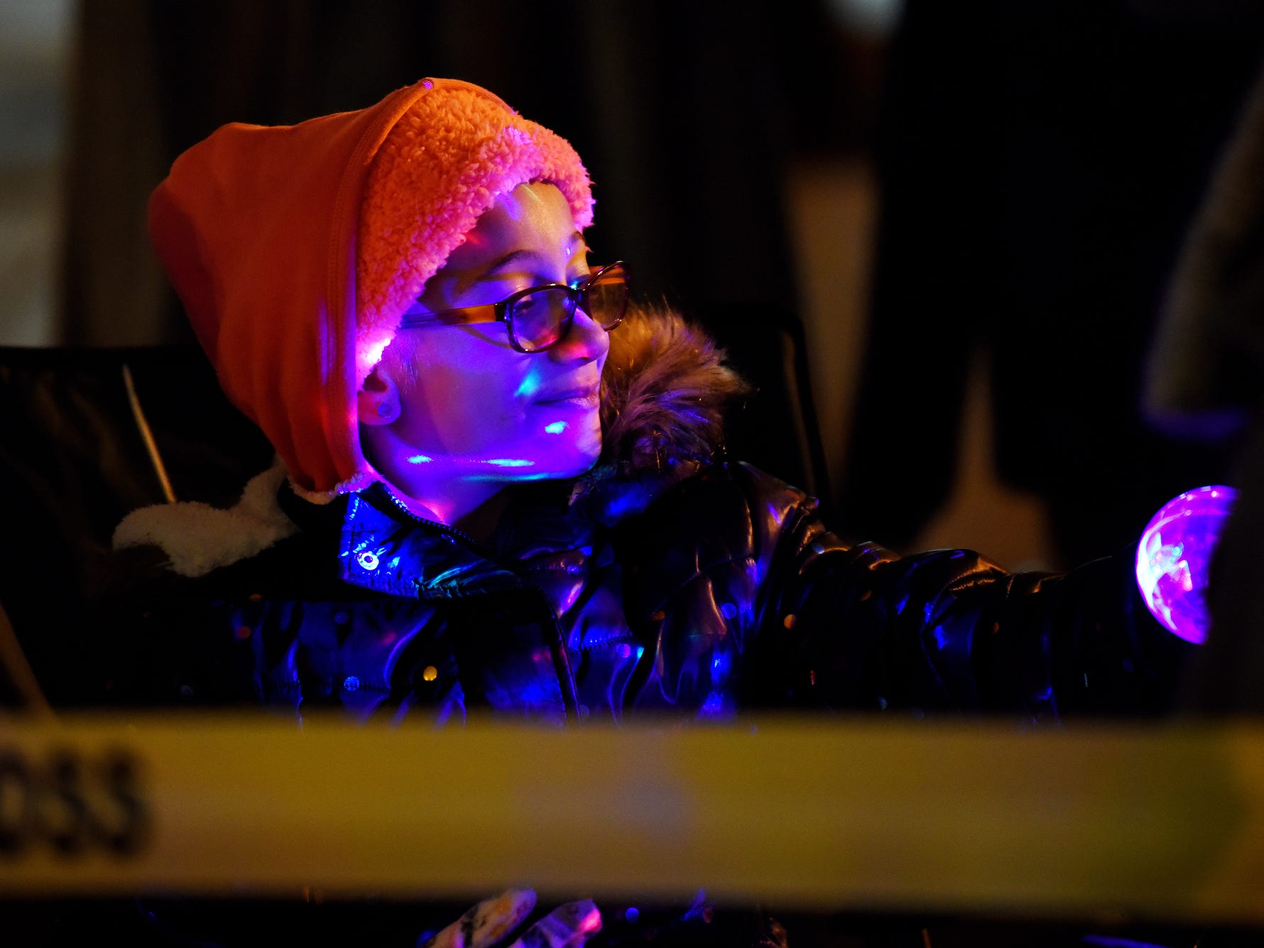 Makayla Stephens, 6, shines colored lights on her face as she watches the Electric Light Parade during the Silver Bells in the City on Friday, Nov. 16, 2018, in downtown Lansing.