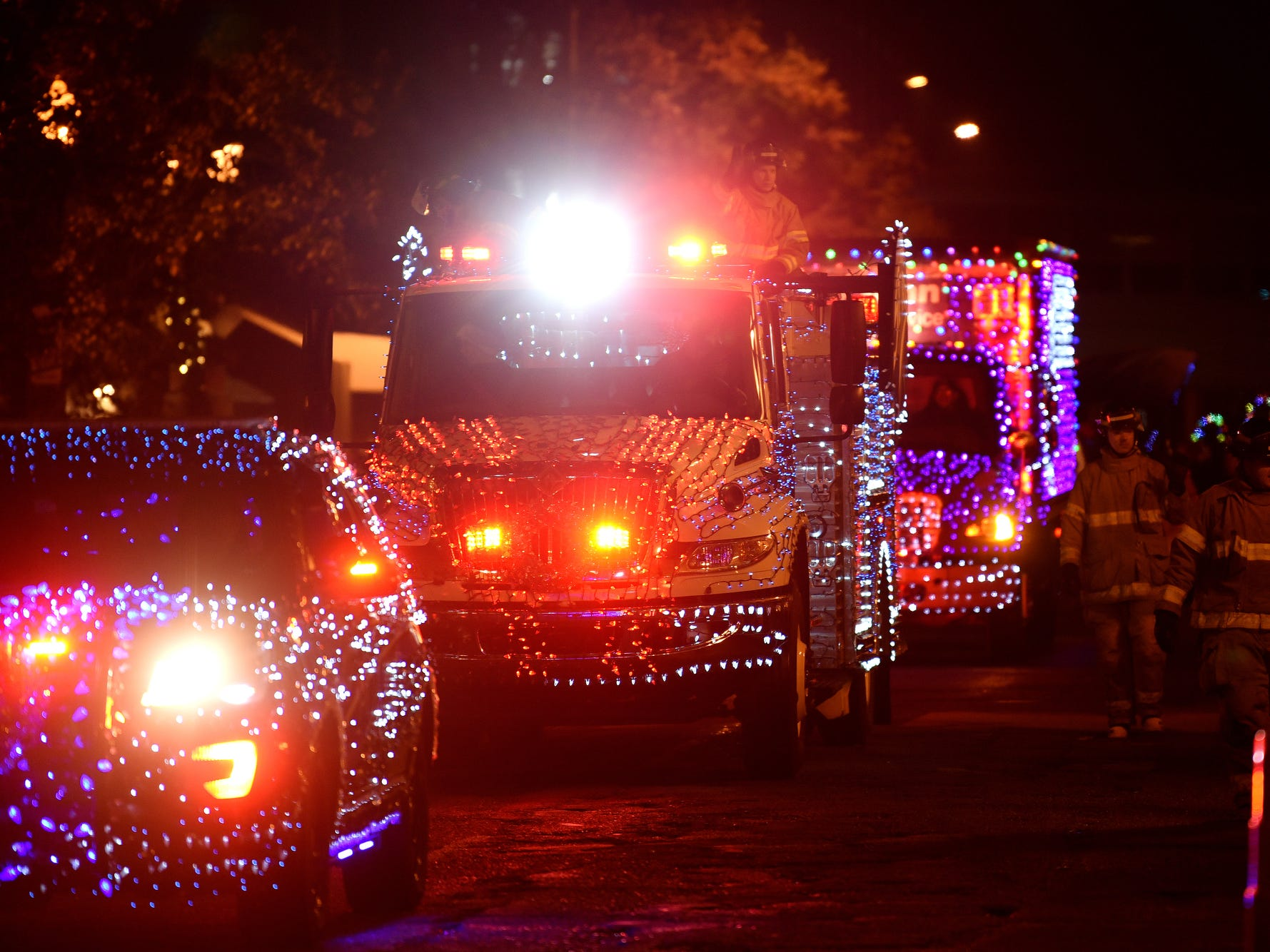 Lansing Community College police and fire vehicles move along the route during the Silver Bells in the City Electric Light Parade on Friday, Nov. 16, 2018, in downtown Lansing.