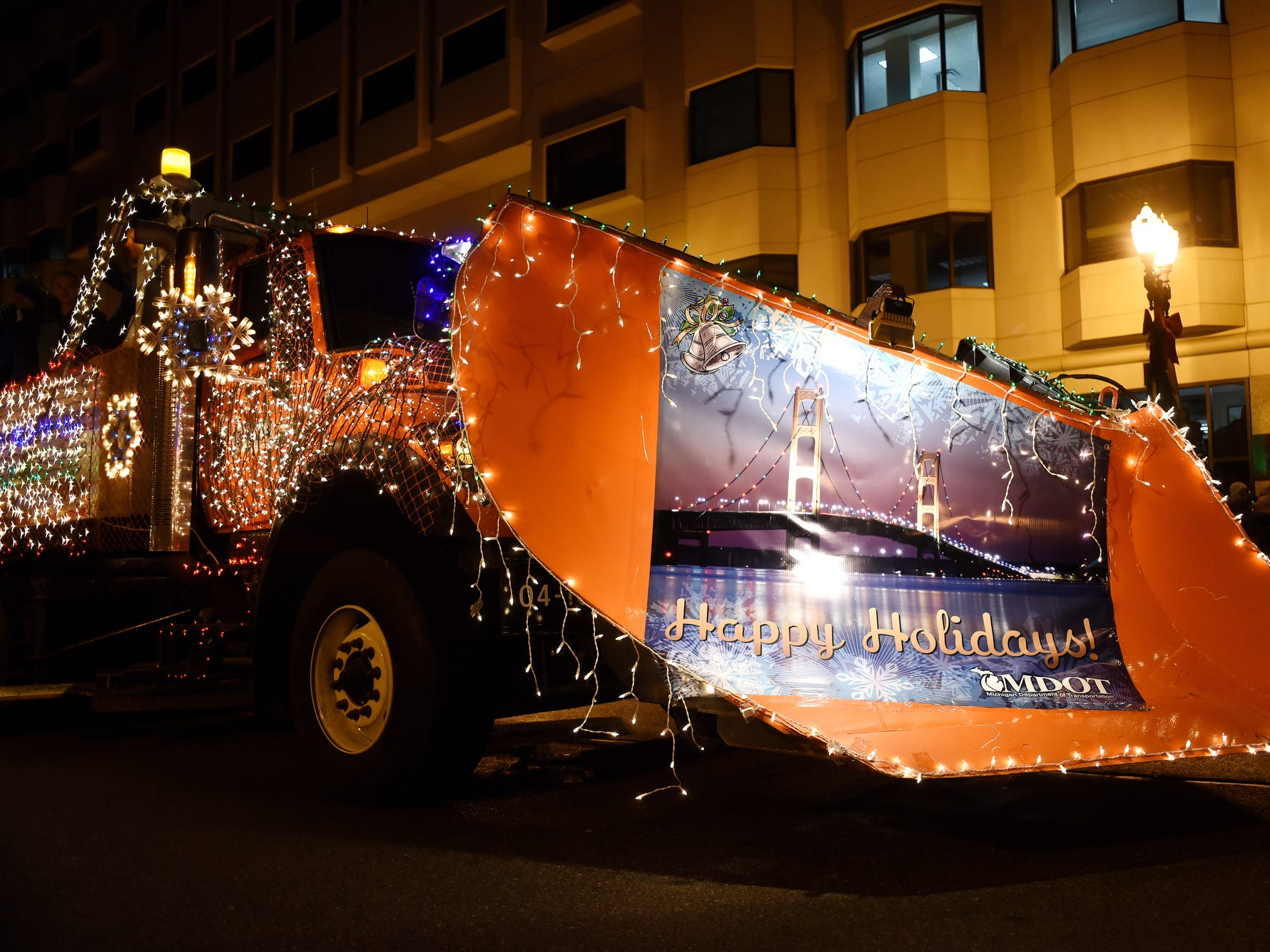 A MDOT truck passes spectators during the Silver Bells in the City Electric Light Parade on Friday, Nov. 16, 2018, in downtown Lansing.