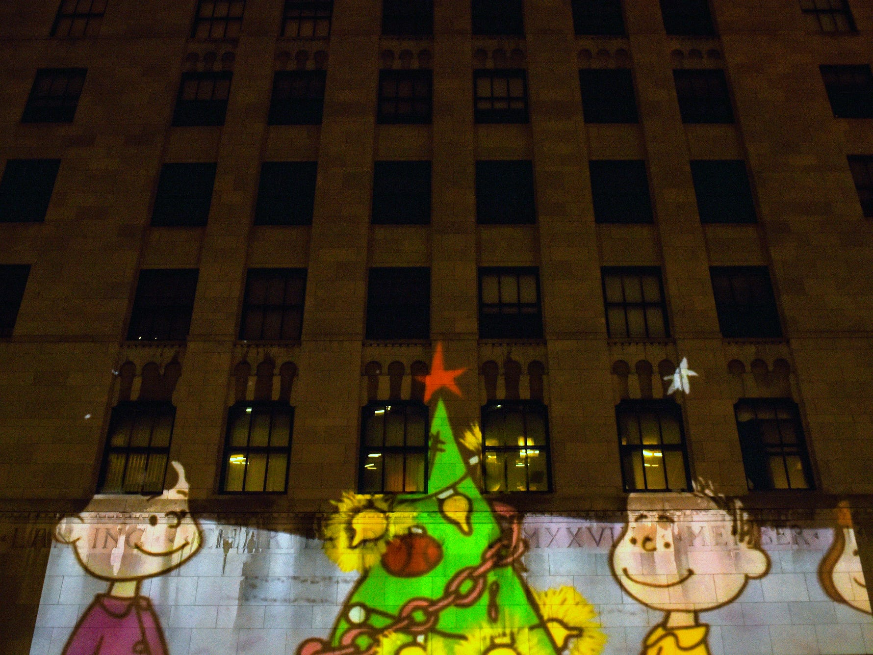 "A scene from ""A Charlie Brown Christmas"" is projected on the side of a building on Michigan Avenue during the Silver Bells in the City Electric Light Parade on Friday, Nov. 16, 2018, in downtown Lansing."