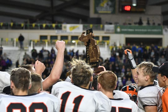 Morrice players celebrate with the 8-Player Division State Championship trophy after the Orioles' 44-16 title game win over Pickford on Saturday at the Super Dome in Marquette.