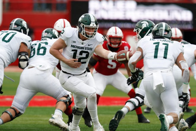 Nov 17, 2018; Lincoln, NE, USA; Michigan State Spartans quarterback Rocky Lombardi (12) hands off to running back Connor Heyward (11) during the game against the Nebraska Cornhuskers in the first half at Memorial Stadium. Mandatory Credit: Bruce Thorson-USA TODAY Sports