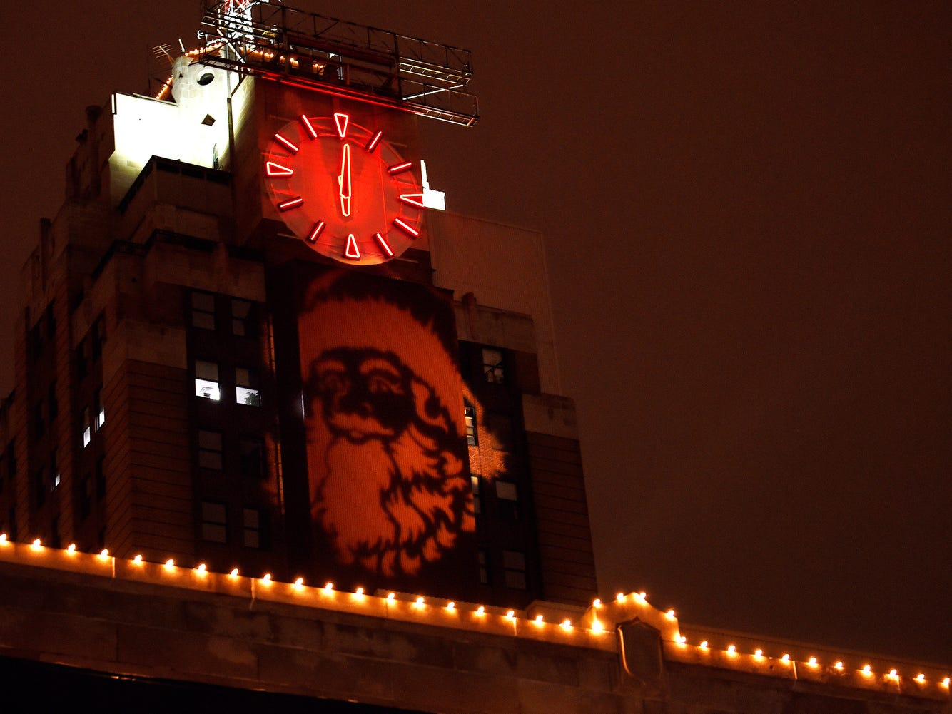 An image of Santa is projected onto the Boji Tower as a spectator watches from the window of a building on Washington Square during the Silver Bells in the City Electric Light Parade on Friday, Nov. 16, 2018, in downtown Lansing.