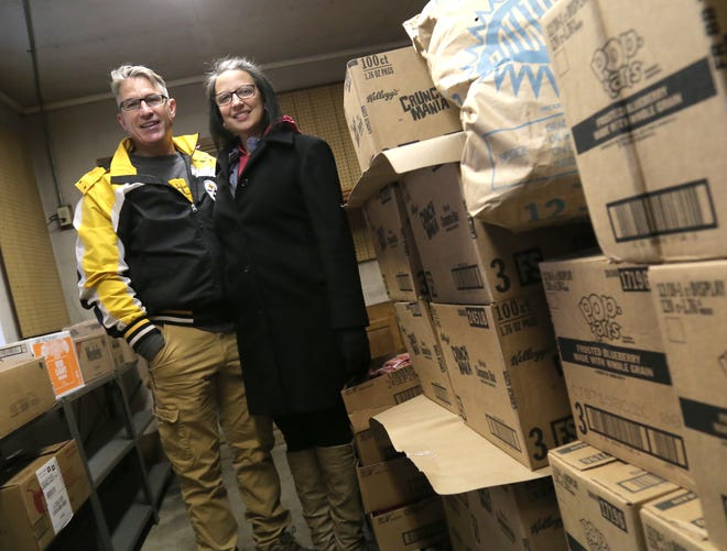 Andrea and Anthony Horning, founders of Emmanuel's Bread, stand next to food in their storage area in Crestline.