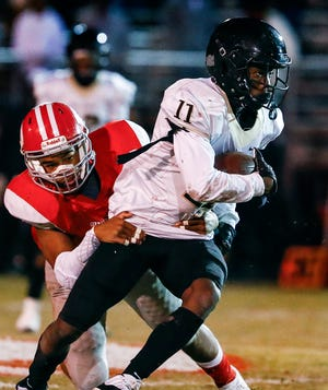 Whitehaven running back Cameron Sneed (right) is brought down by Germantown defender Kenneth Hatch (left) during action of their 6A state playoff game in Germantown, Tenn.
