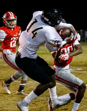 Whitehaven receiver Keveon Mullins (left) grabs a first-down catch away from Germantown defender Chris Williams (right).