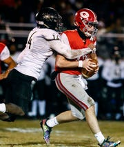 Germantown quarterback Ethan Payne (right) its tackled by Whitehaven defender Keveon Mullins (left) during action of their 6A state playoff game in Germantown, Tenn.