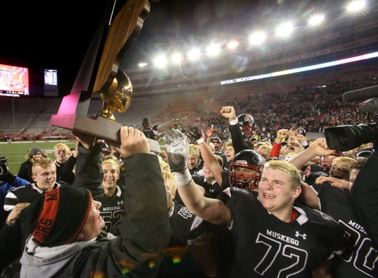 Muskego Football Coach Ken Krause presents the team with the WIAA Division 1 championship trophy.