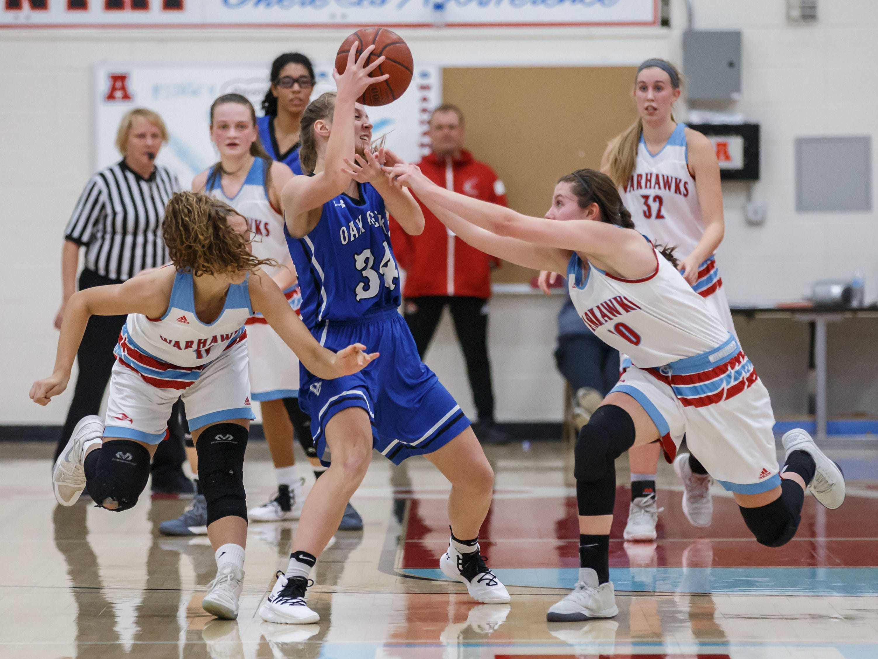 Oak Creek sophomore Jamie Finn (34) battles Arrowhead's Anna Oehmcke (left) and Emily Giese during the game in Hartland on Friday, Nov. 16, 2018.
