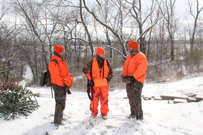 Mark Schack (left) of Tomah and his son, Matthew Schack (right) of Fitchburg,  talk with Will Kramer of Dodgeville after a morning hunt on land owned by Will's parents, Kent and Amy Kramer, on opening day of the 2018 Wisconsin gun deer hunting season.