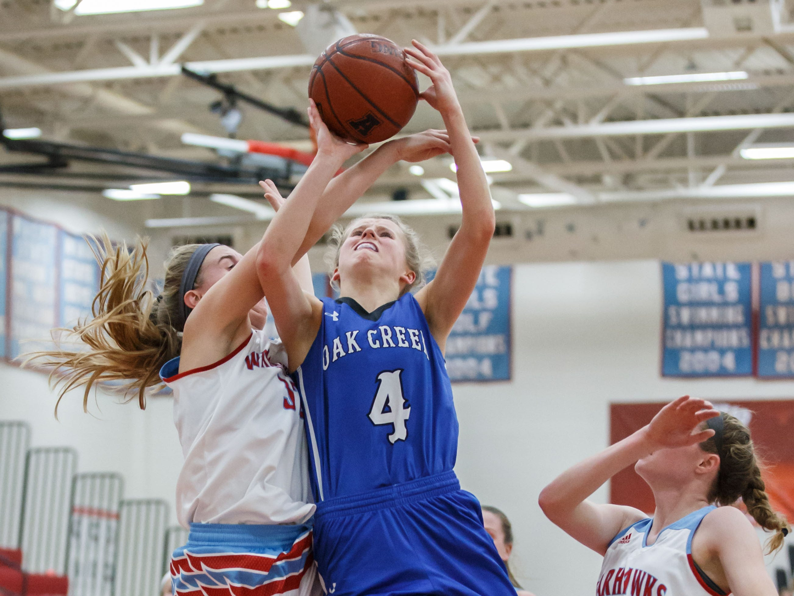 Oak Creek senior Maddie Gard (4) gets fouled by Arrowhead's Lauren With (32) during the game in Hartland on Friday, Nov. 16, 2018.