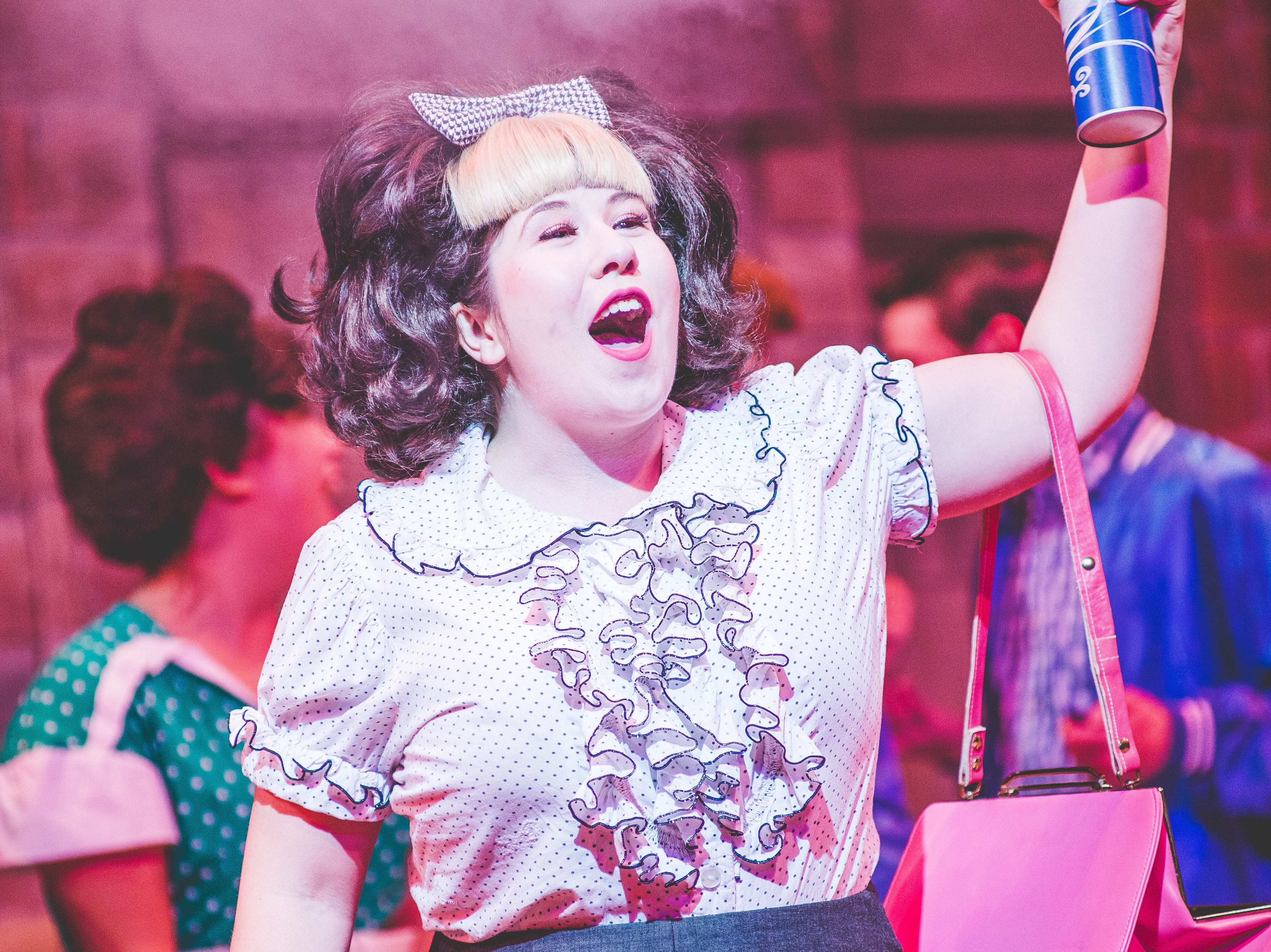 """Maisie Rose applies the title product in Skylight Music Theatre's """"Hairspray."""""""