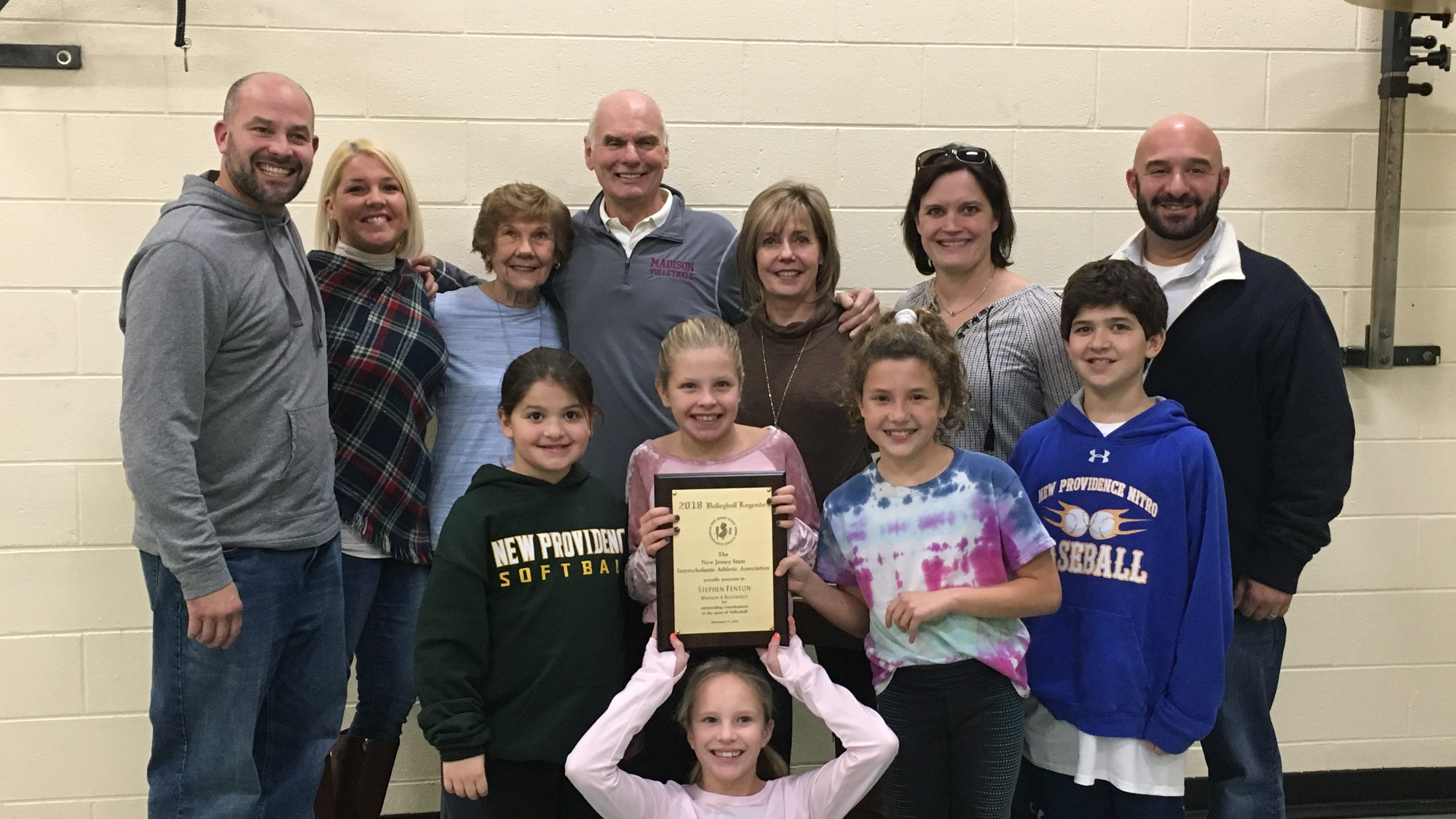 Madison coach Stephen Fenton (center) and new NJSIAA Volleyball Legend receives congratulations from his mother, Lorraine (left), wife Karen (right), children Jennifer Kessler and Stephen Fenton Jr., and their spouses and children.