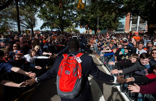 Fans high five players during the Tiger Walk at Jordan-Hare Stadium in Auburn, Ala., on Saturday, Nov.. 17, 2018.
