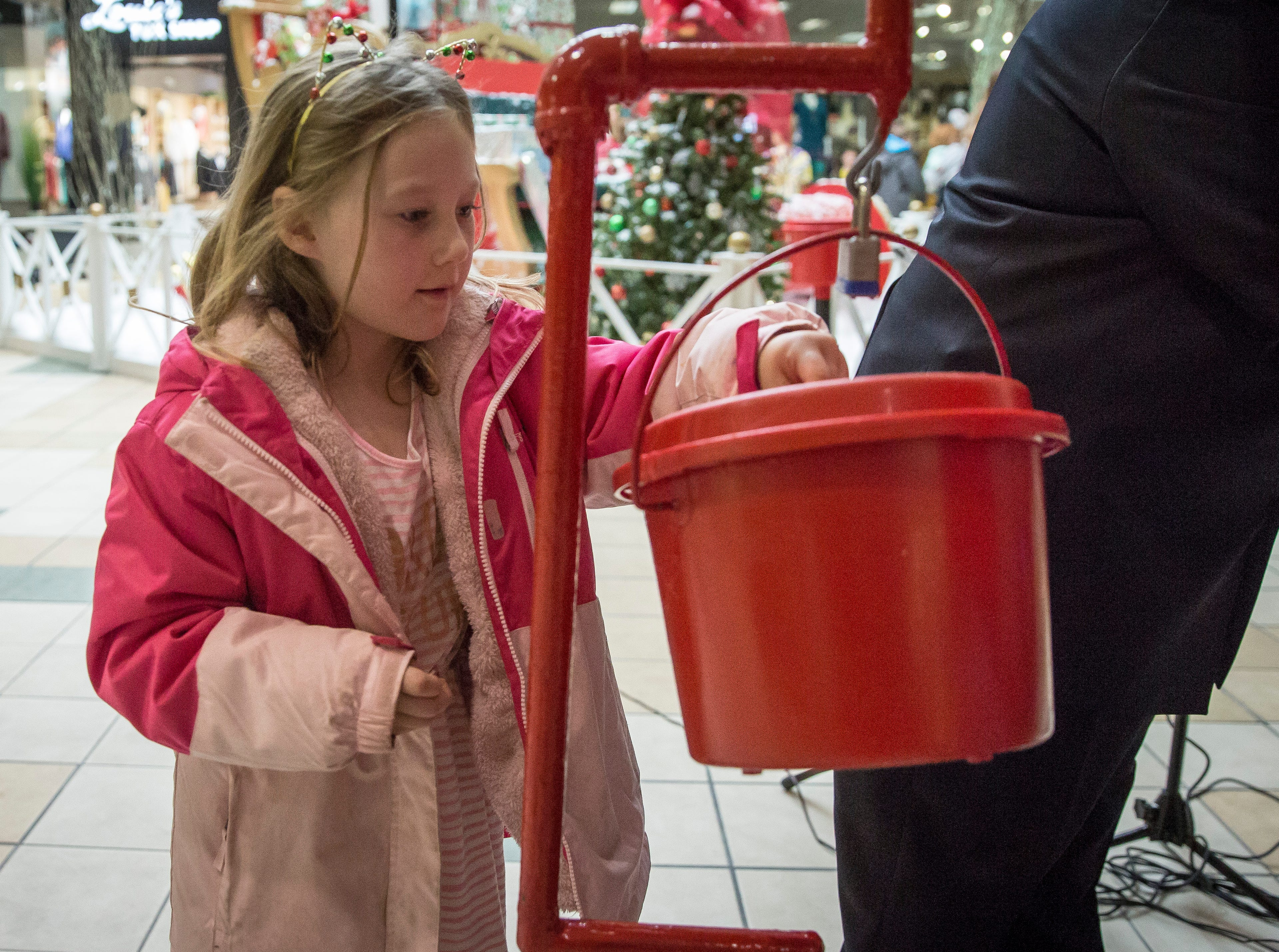 Children help put money inside the red kettles after the Salvation Army's Red Kettle Campaign Kickoff at the Muncie Mall. The long time tradition of bell ringers outside shopping centers is just one way to donate to the organization.