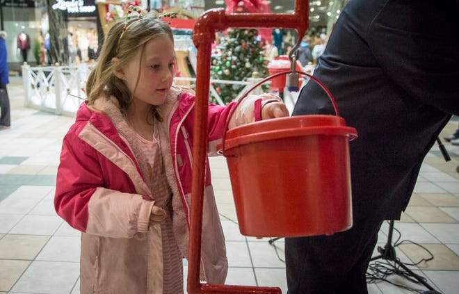 Children help put money inside the red kettles after the Salvation Army's Red Kettle Campaign Kickoff at the Muncie Mall IN 2018.