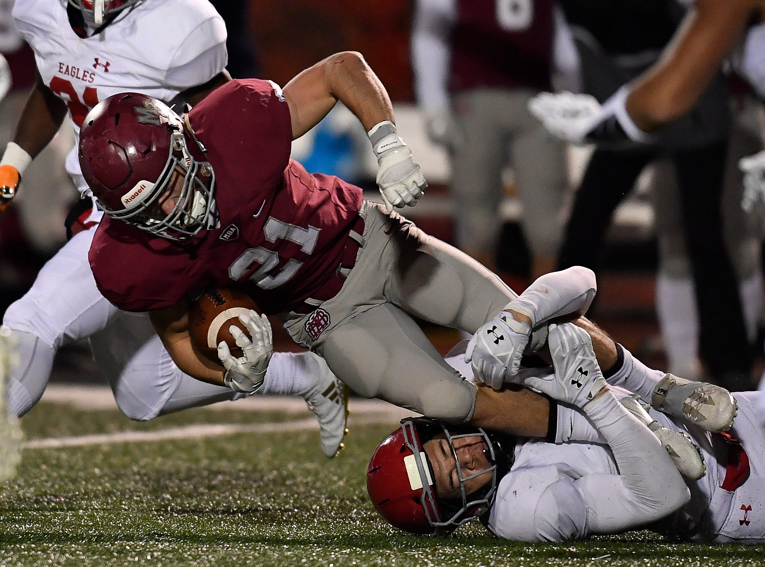 MBA running back Sam Dugan (21) is pulled down by a Brentwood Academy defender during the second quarter of their 2018 Division II Class AAA State Football Playoff game at Montgomery Bell Academy Friday, Nov. 16, 2018, in Nashville, Tenn.